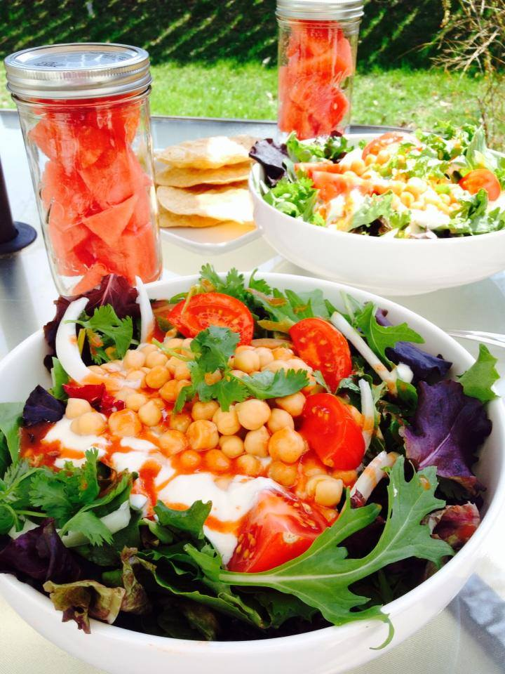 Lunch time salads topped with homemade plant based yogurt & hot sauce with a jar…